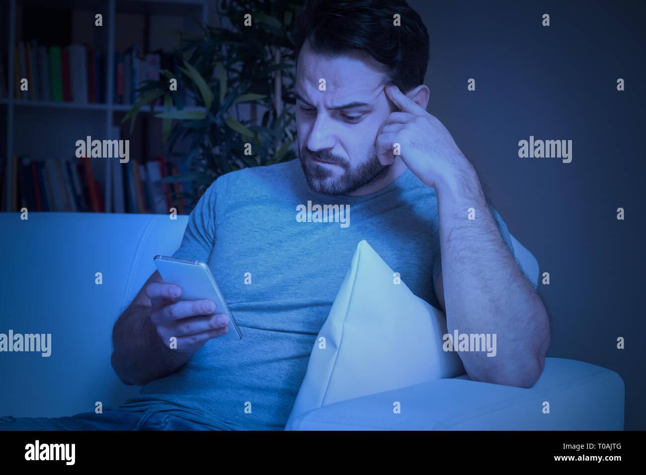 Sad man holding mobile phone feeling bad - Stock Image