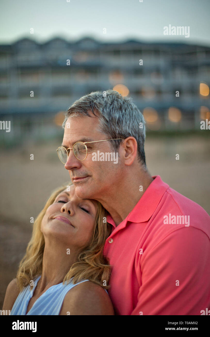 Woman relaxing into her husband's embrace on the beach at sunset. - Stock Image