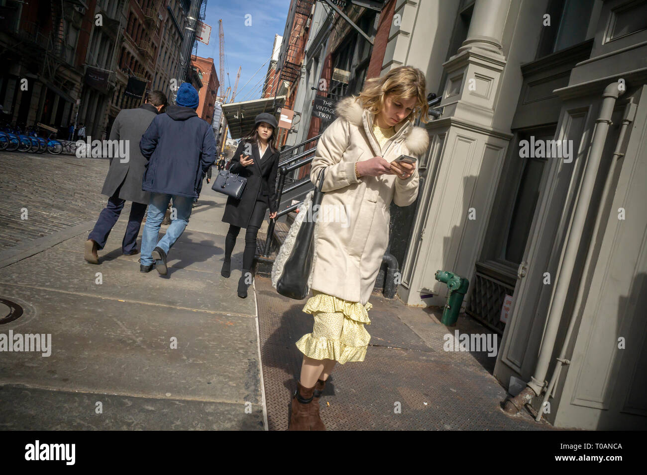 A distracted woman, engrossed in her smartphone, in Soho in New York on Thursday, March 14, 2019.  (© Richard B. Levine) - Stock Image
