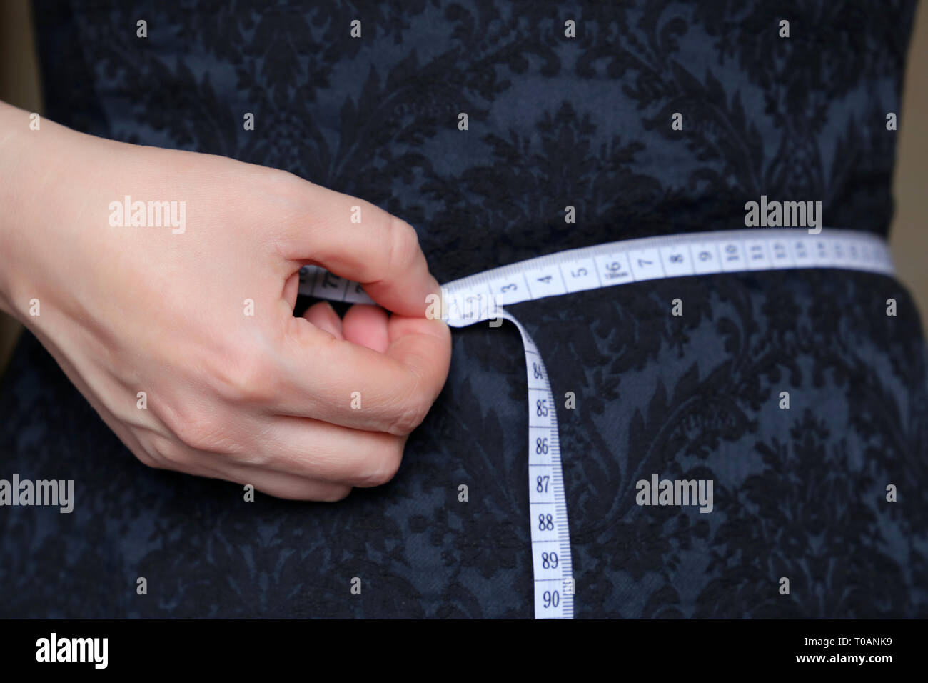 Weight loss, slimming, diet concept. Girl in blue dress with measuring tape around the waist - Stock Image