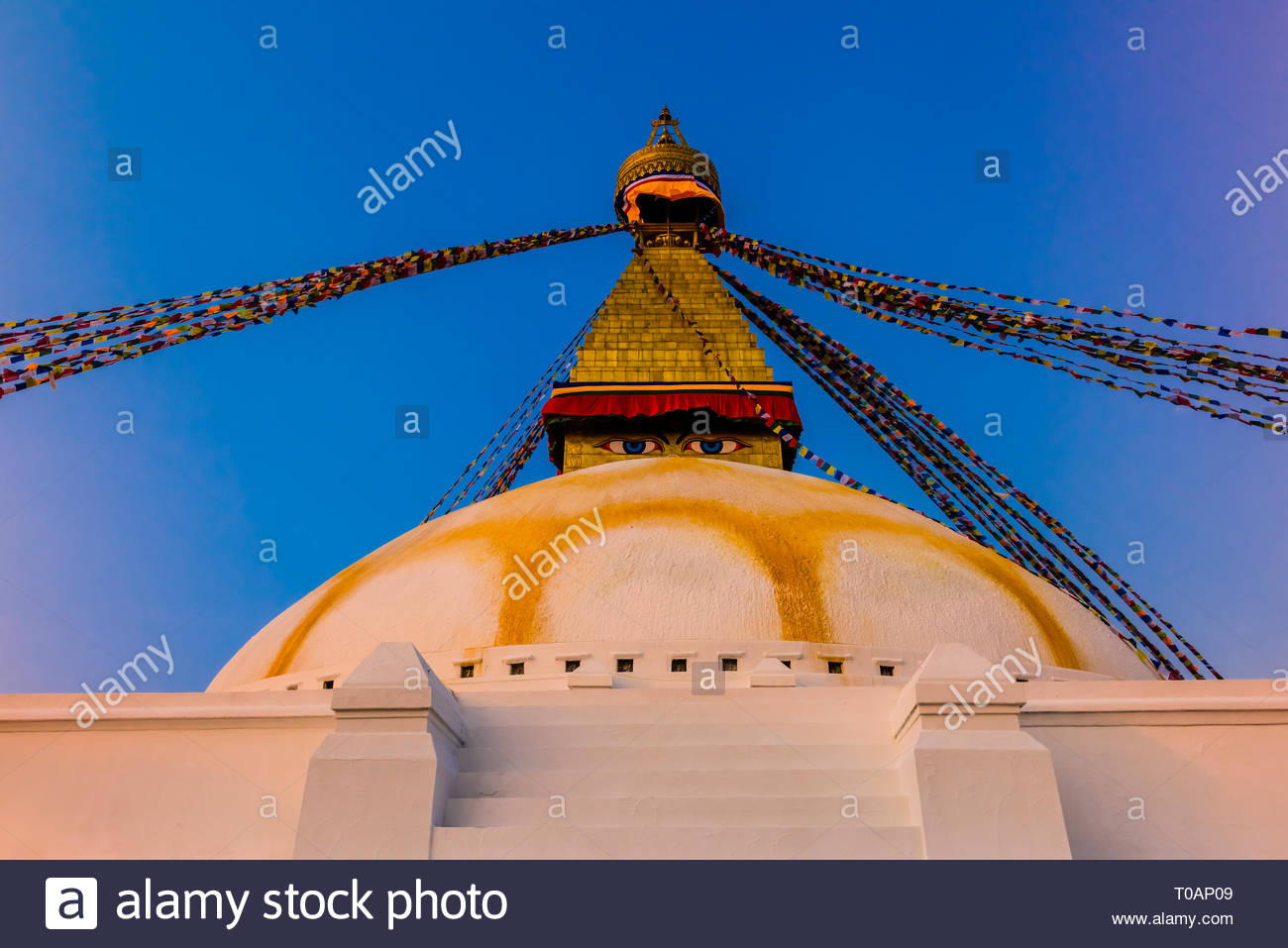 Prayer flags ring the massive stupa of the Boudhanath Temple. It is the largest stupa in Nepal and the holiest Tibetan Buddhist temple outside Tibet.  - Stock Image