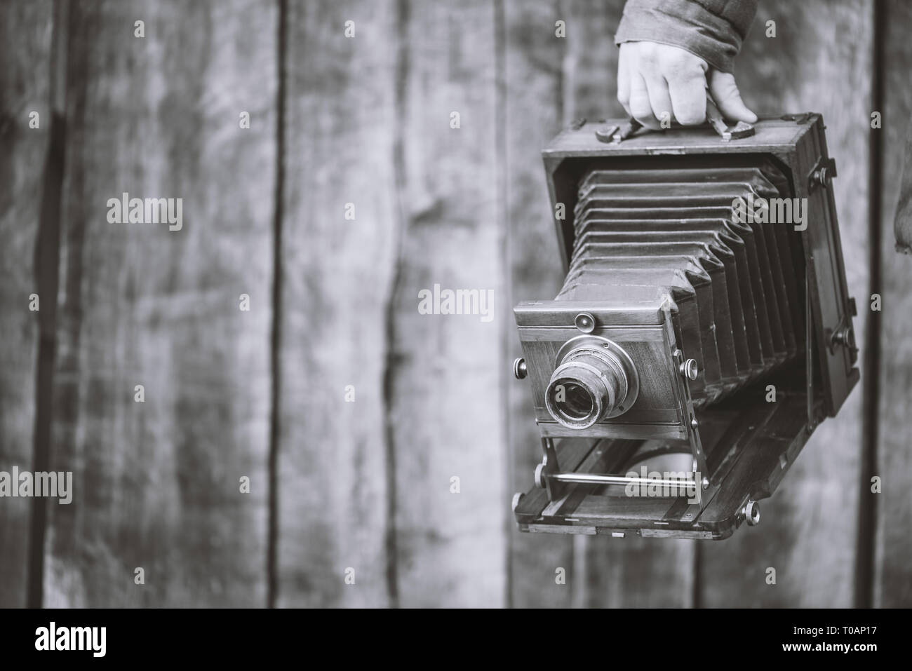 Large format retro camera, 5x7 inches. Photographer holds in hand old studio camera. Monochrome effect, copyspace. Concept - photography of the 1930s- - Stock Image