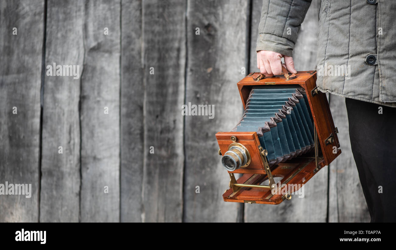 Large format retro camera in photographer hand. Concept - photography of the 1930s-1950s. Retro wooden wall on background, copy space for text - Stock Image