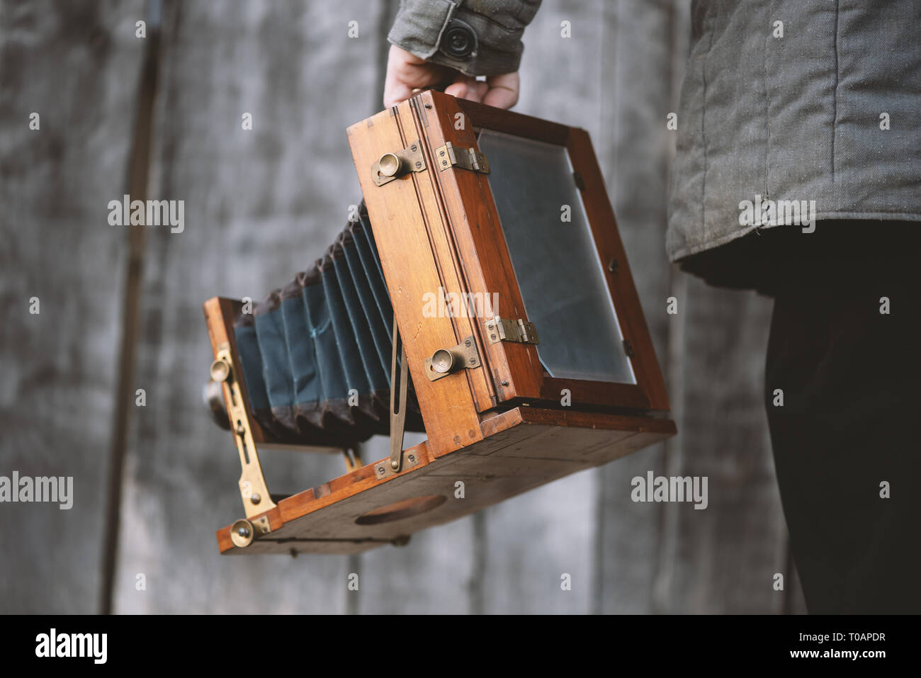Photographer holds vintage large format studio camera, 5x7 inches. Concept - photography of the 1930s-1950s. - Stock Image