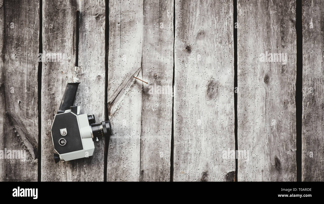 Old fashioned film camera hanging on wooden wall. Concept - movie of the 1970s-1980s - Stock Image