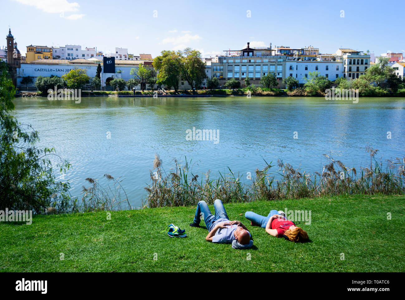 A young couple having a siesta beside the Guadalquivir River in Seville - Stock Image