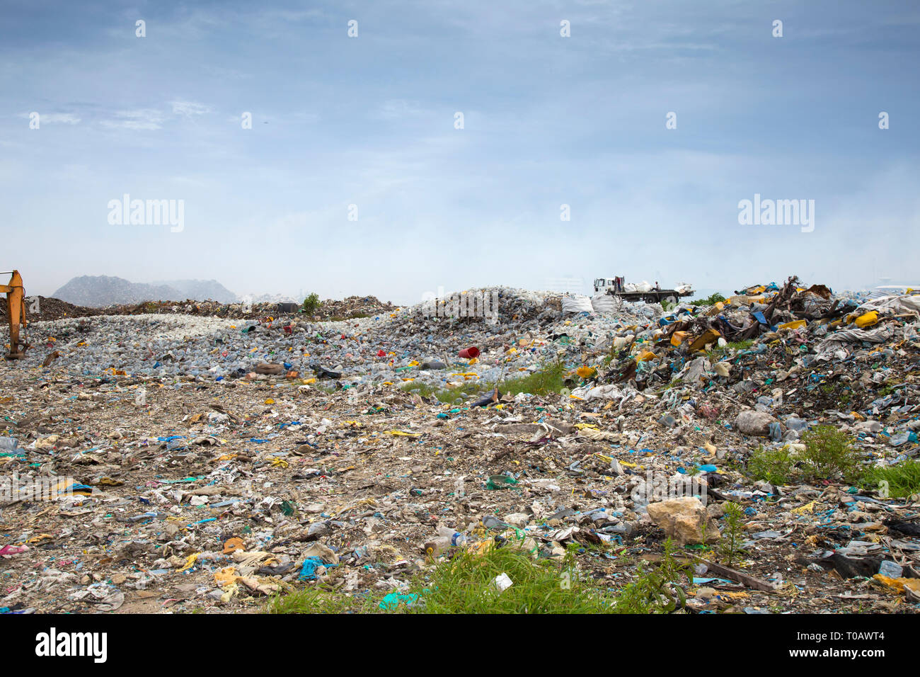 Open landfill area covered with plastic bottles, which ultimately going to burn - Stock Image