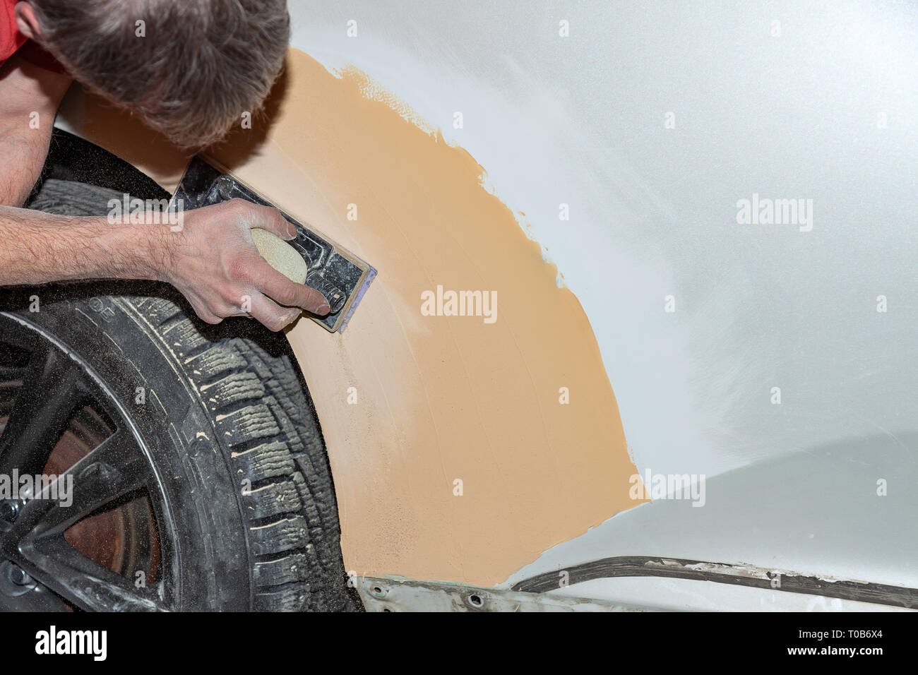 Preparation for painting a car element using emery sender by a service technician leveling out before applying a primer after damage to a part of the  - Stock Image
