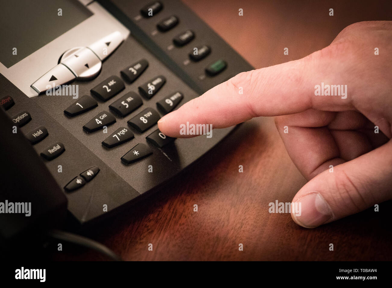 Finger dialing phone call on touch tone telephone. - Stock Image