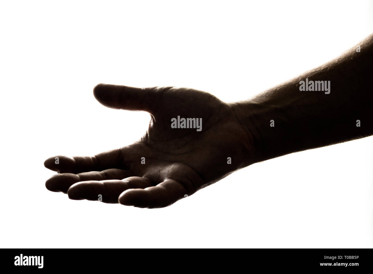Silhouette of hand reaching out to give, or to receive help/money/hope/gift. - Stock Image