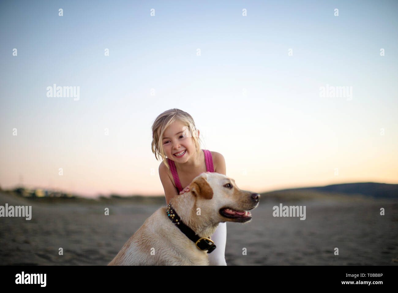 Portrait of a happy young girl smiling as she plays with her dog on the beach at dawn. Stock Photo