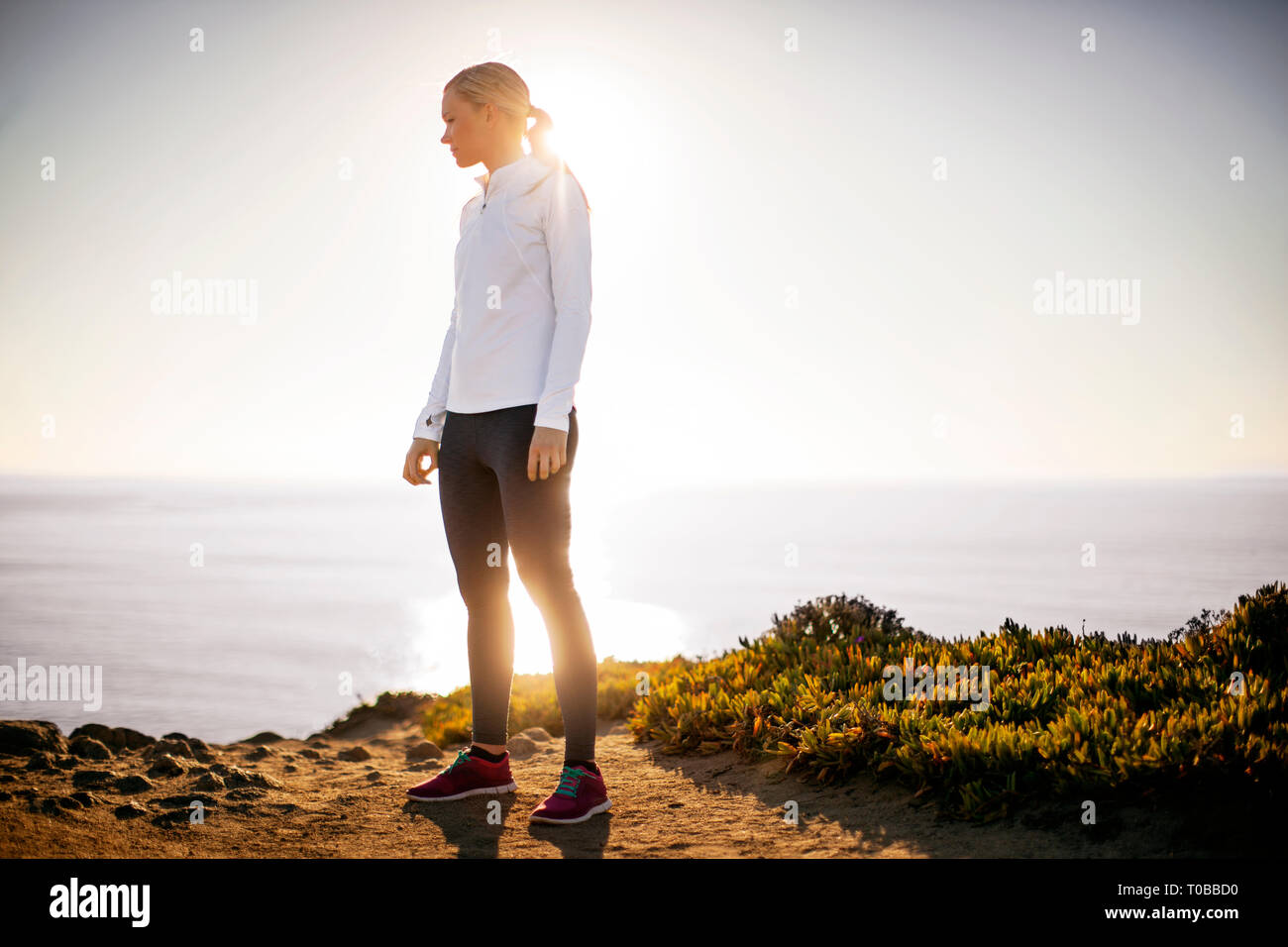 Young woman takes a break from her sunrise jog along the cliffs to admire the view of the ocean. Stock Photo