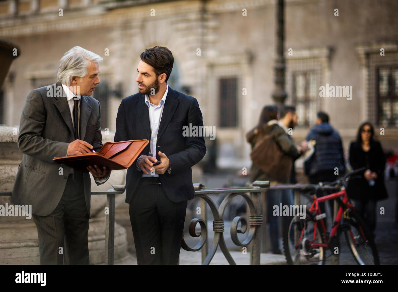 Mature businessman has a chance meeting with a young colleague while they are out in the city. - Stock Image