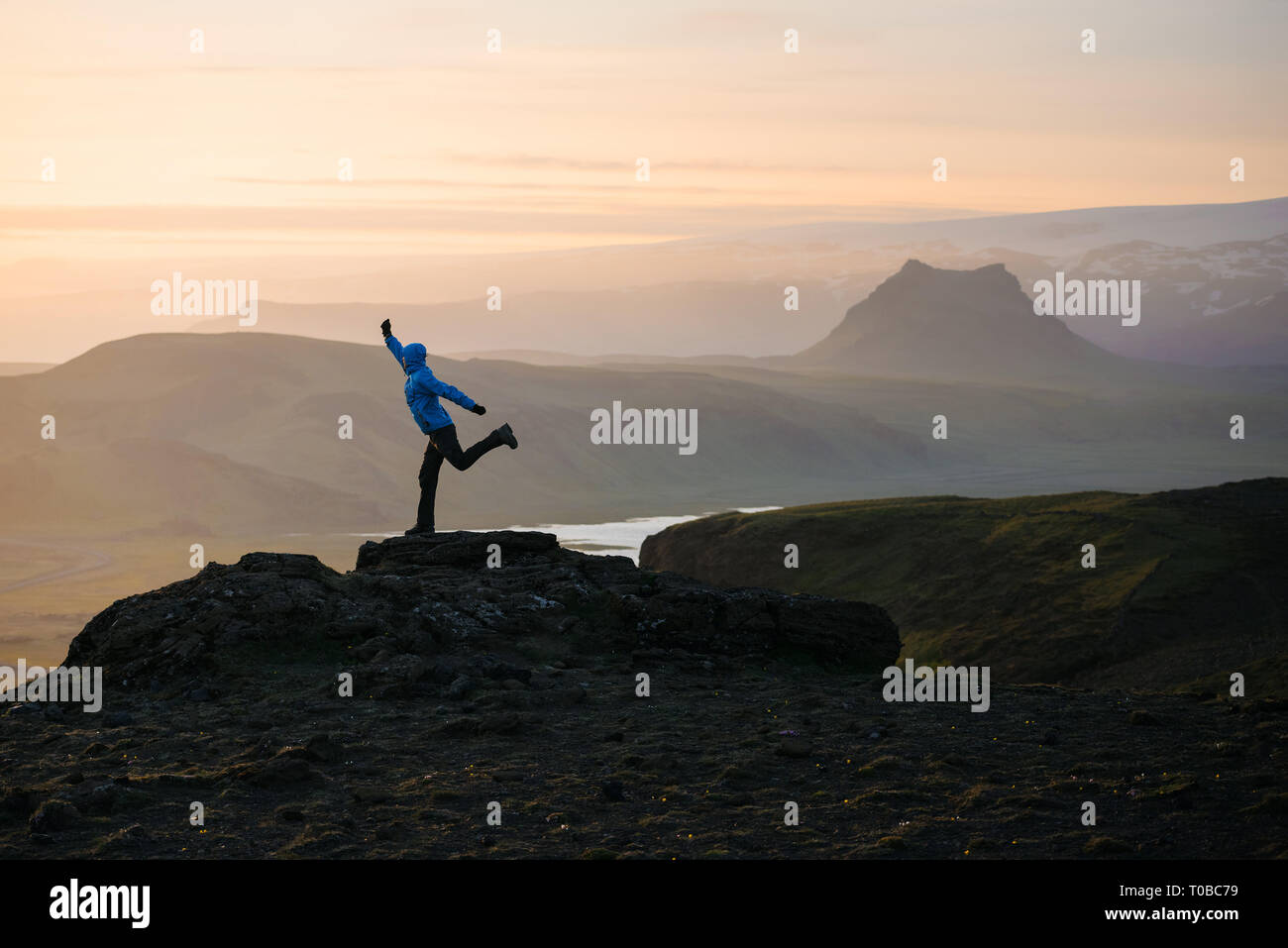 Adventure in the mountains of Iceland. Tourist is standing on a rock against the background of the setting sun. Location near Dyrholaey Cape in southe - Stock Image