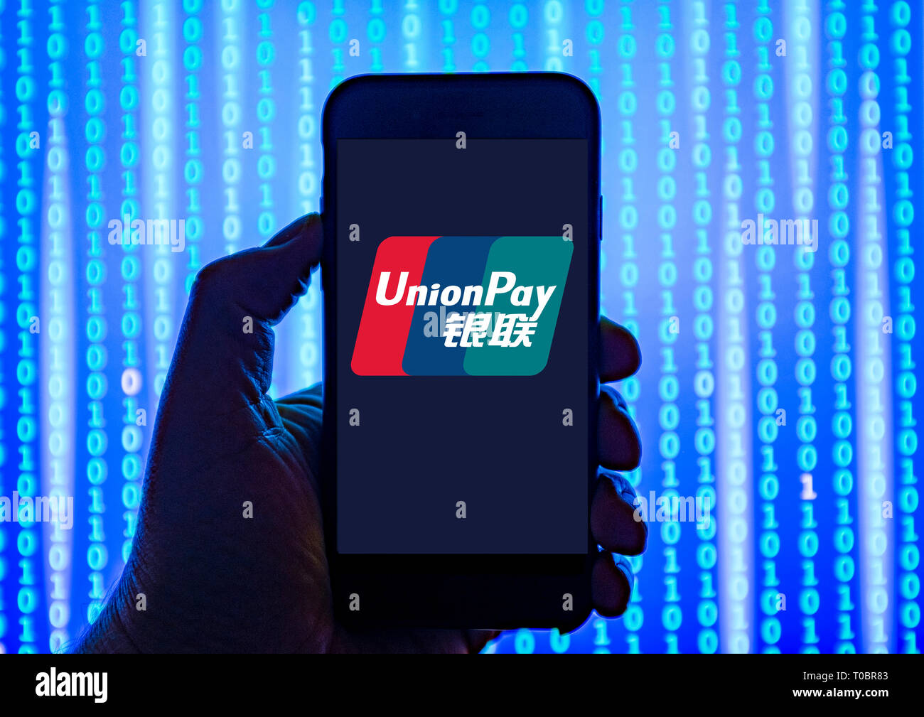 Person holding smart phone with UnionPay logo displayed on the screen. UnionPay fis a Chinese financial services corporation - Stock Image