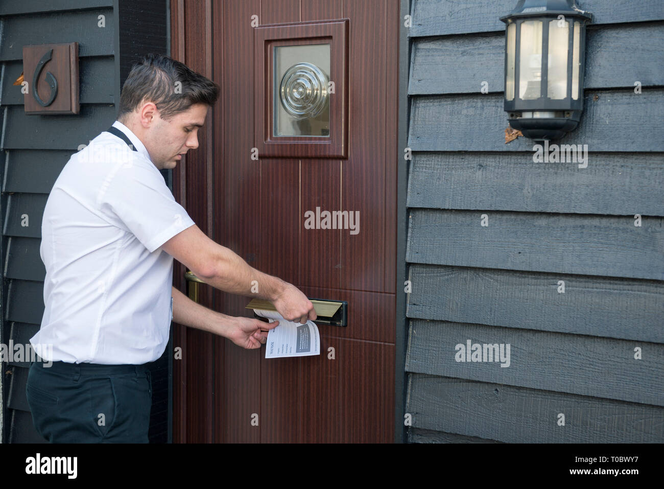 A white male worker / salesman post a letter / note / missed called card for an appointment through the letterbox of a front door of someones home. - Stock Image