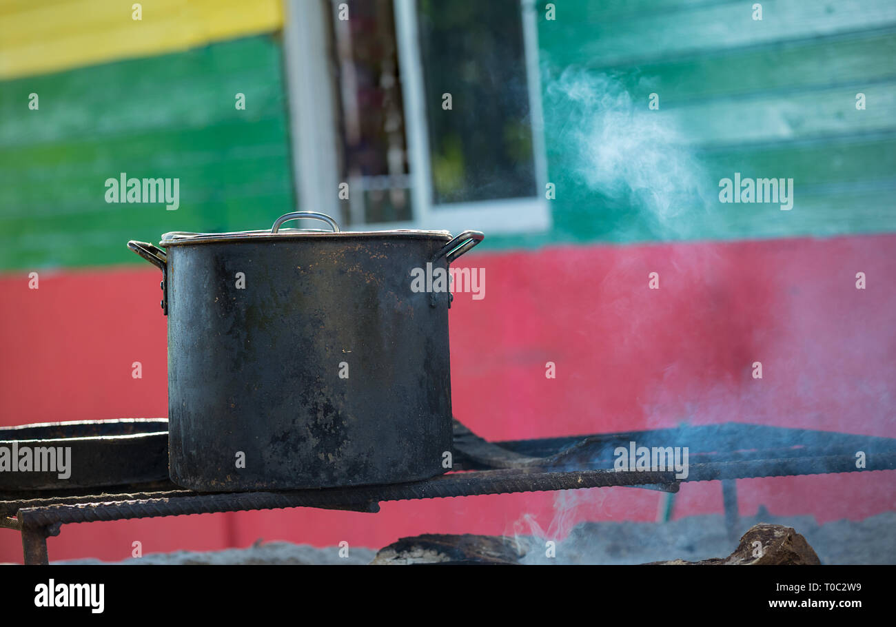 Old dark cooking pot on a wooden fireplace with smoke background - Stock Image