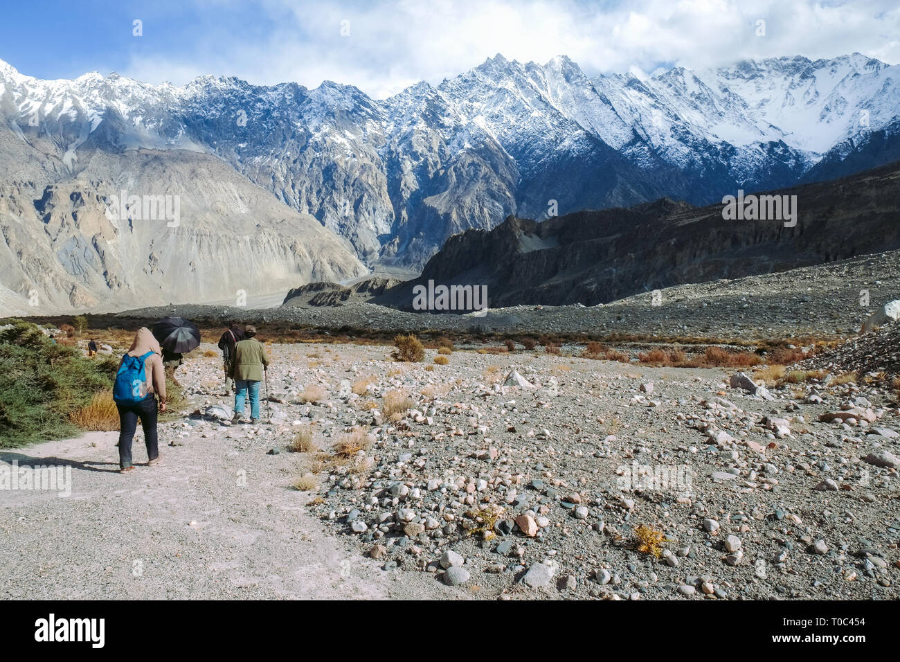 People walking along the trekking trail in Passu. Gilgit, Baltistan, Pakistan. - Stock Image