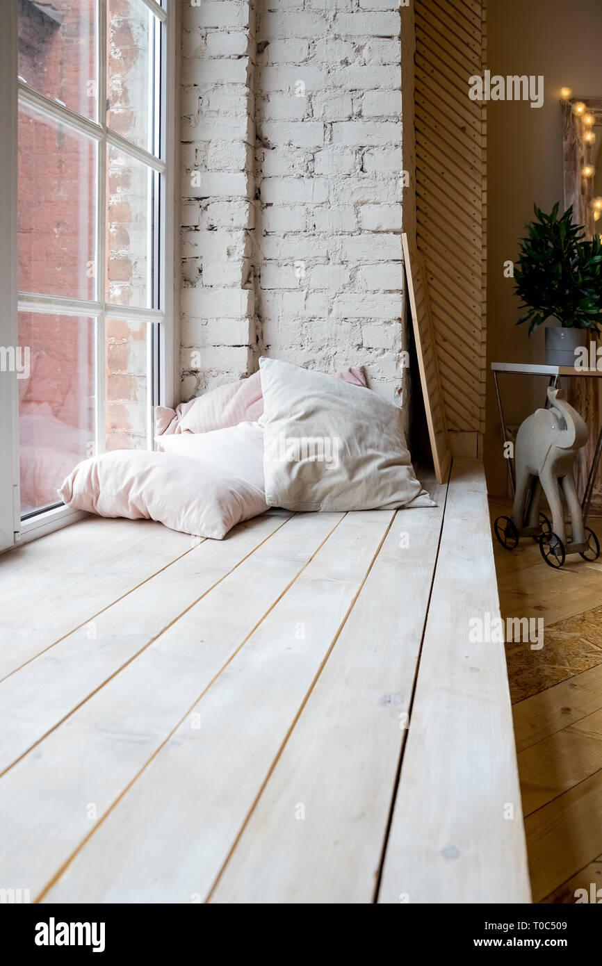 Bright Studio Interior With Big Window, High Ceiling, Wooden Floor.Loft  Style Bedroom Interior Design. Beige Pillows And Brick Wall. Scandinavian