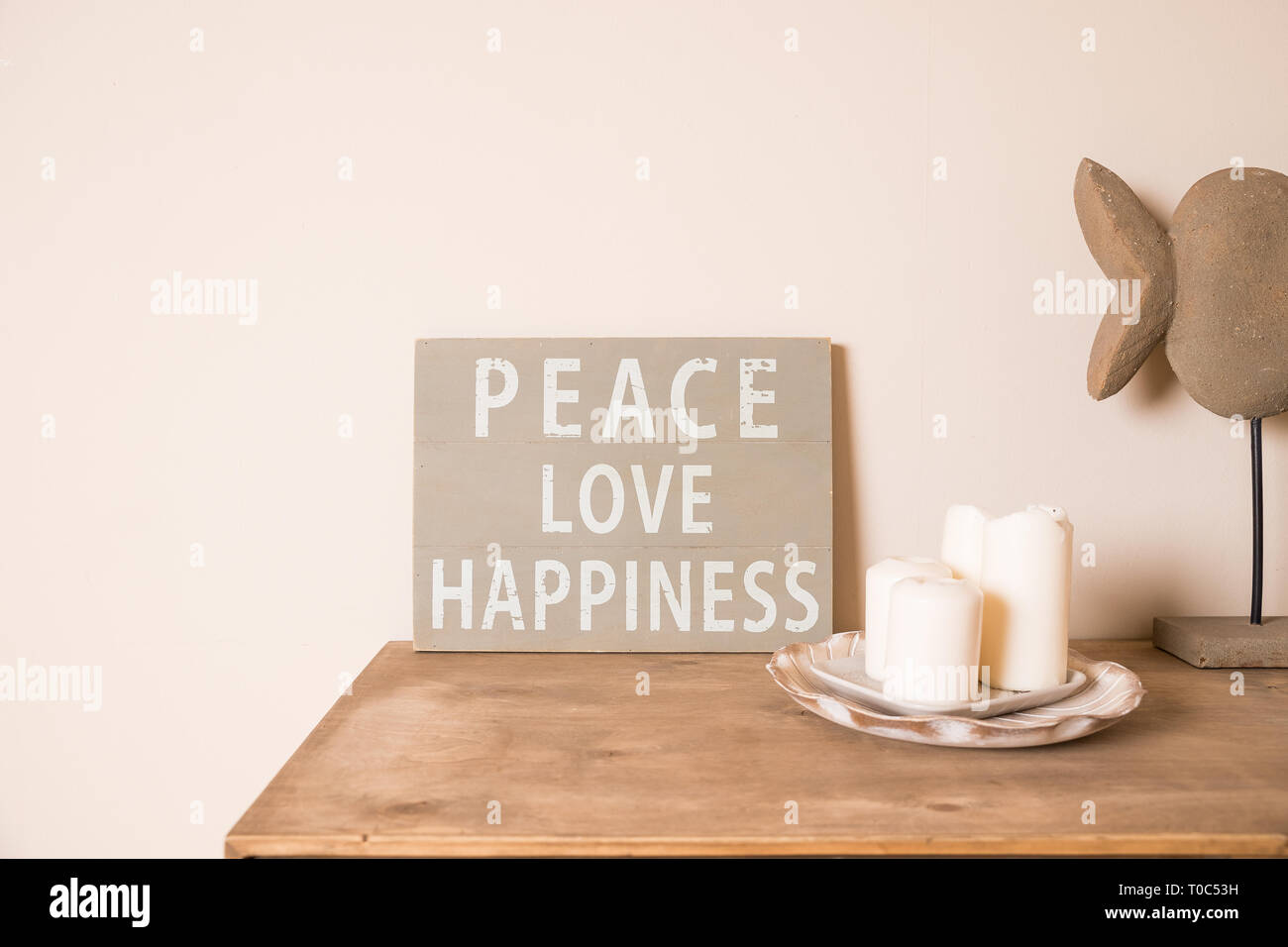 Hipster scandinavian style room interior. Mood board. Old scratched board ,Quote PEACE, LOVE, happiness. White candles,pot with succulents.Rustic Stock Photo