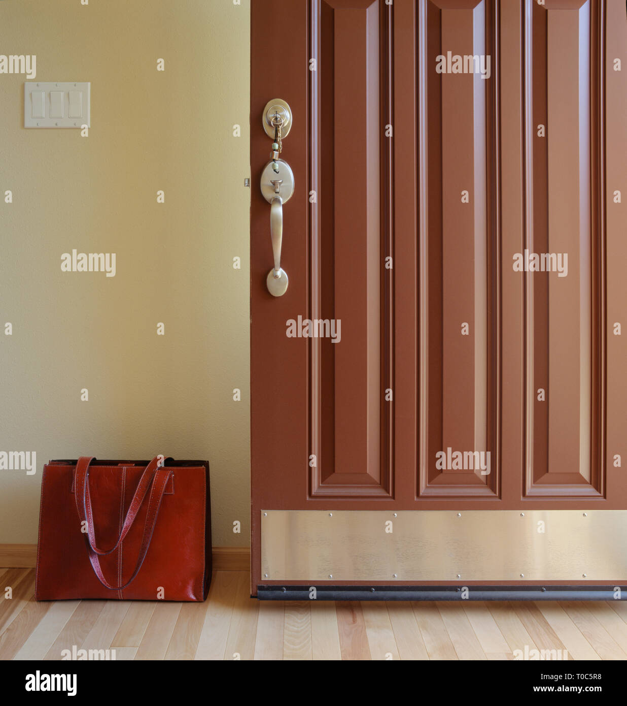 Open front door of house with keys in lock and briefcase brief bag in entry. Coming home from or leaving for work concept. - Stock Image