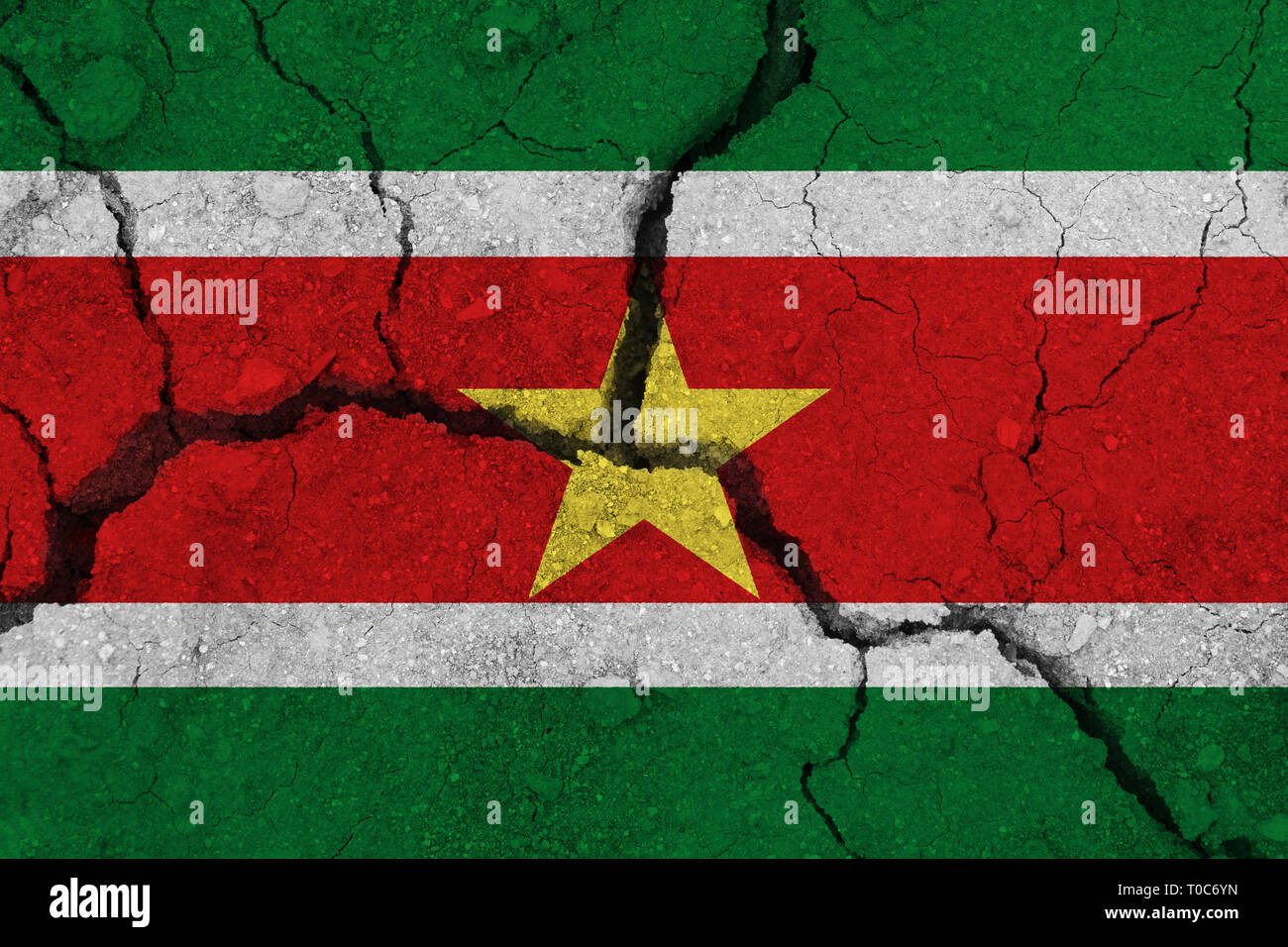 Suriname flag on the cracked earth. National flag of Suriname. Earthquake or drought concept - Stock Image