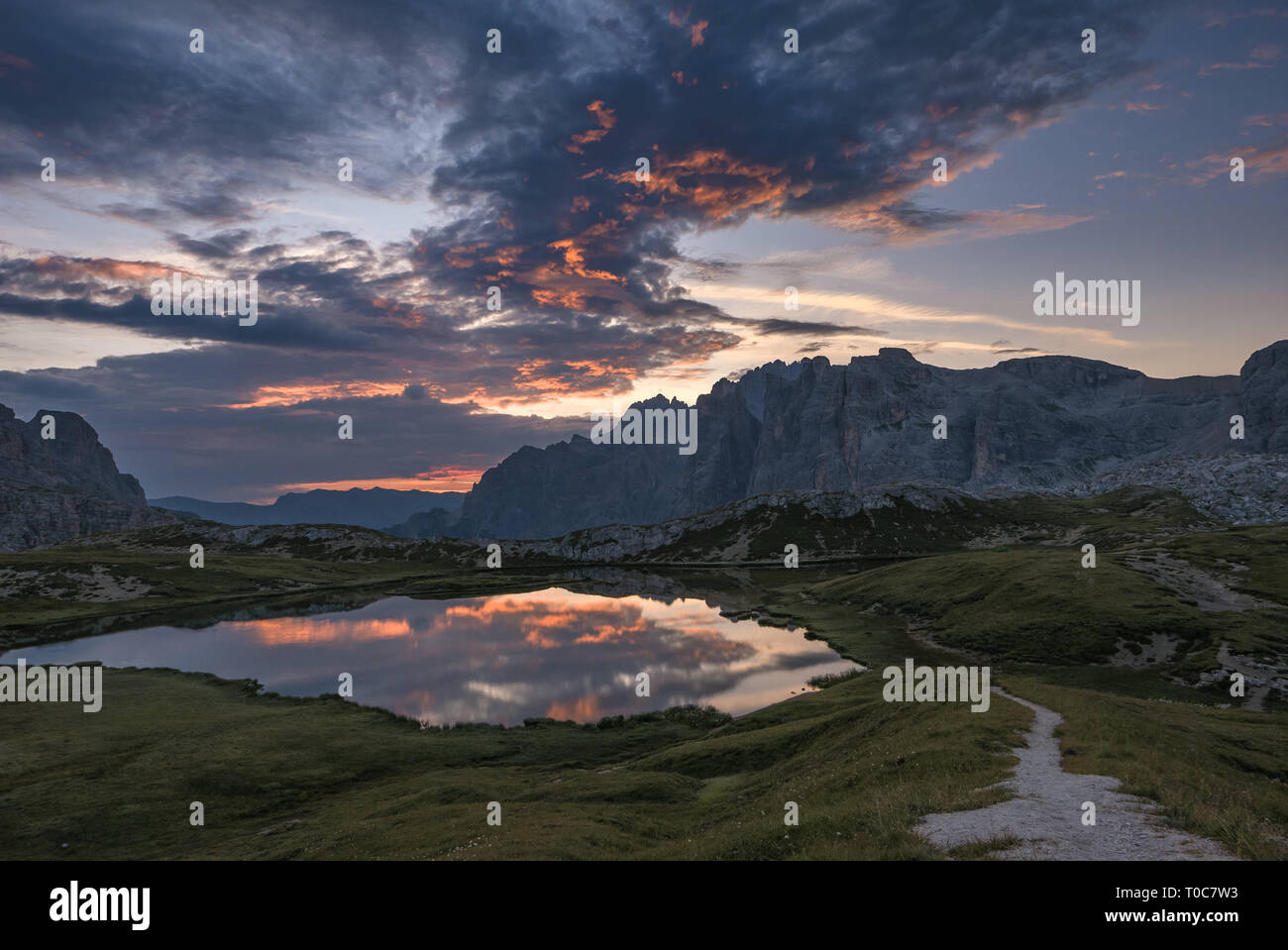 Forces of nature, mountain path and pristine alpine lake - Stock Image