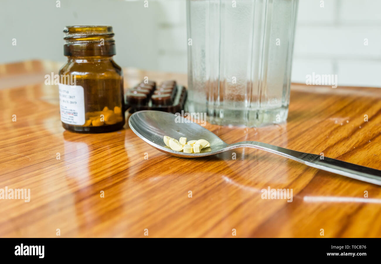 View of antioxidants vitamin tablet, pill blisters, a bottle of drug, capsule in measuring spoon, with glass of water placed on the table. Medical Pha - Stock Image