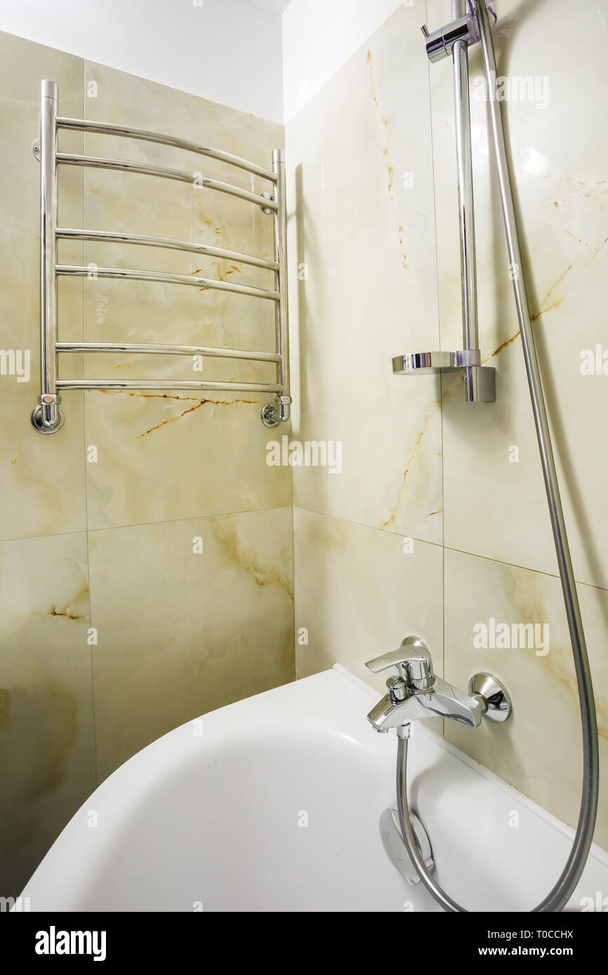 toilet and detail of a corner shower cabin with wall mount shower attachment øò bathroom of hotel - Stock Image