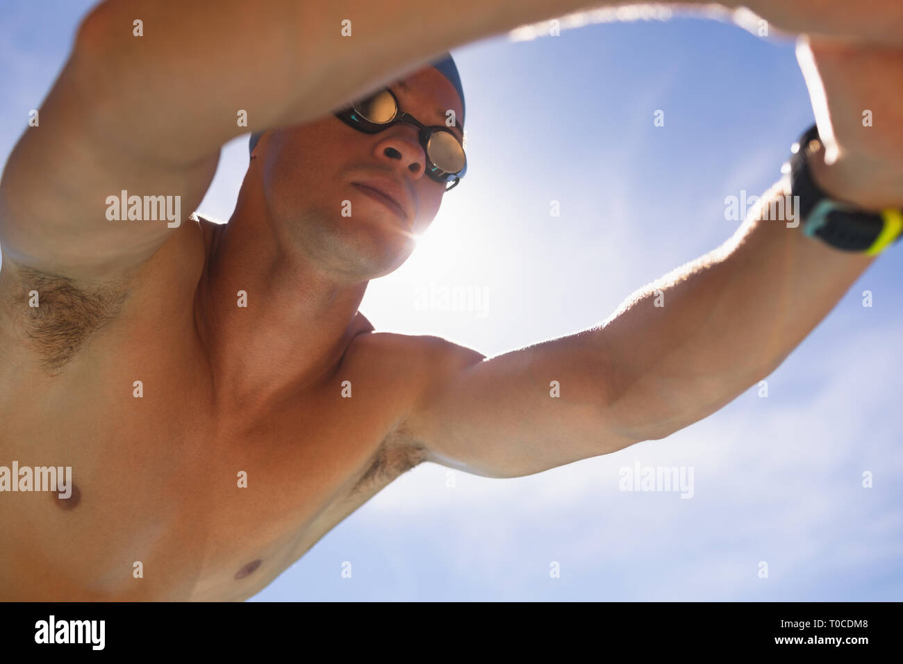 Male swimmer in starting position at swimming pool Stock Photo