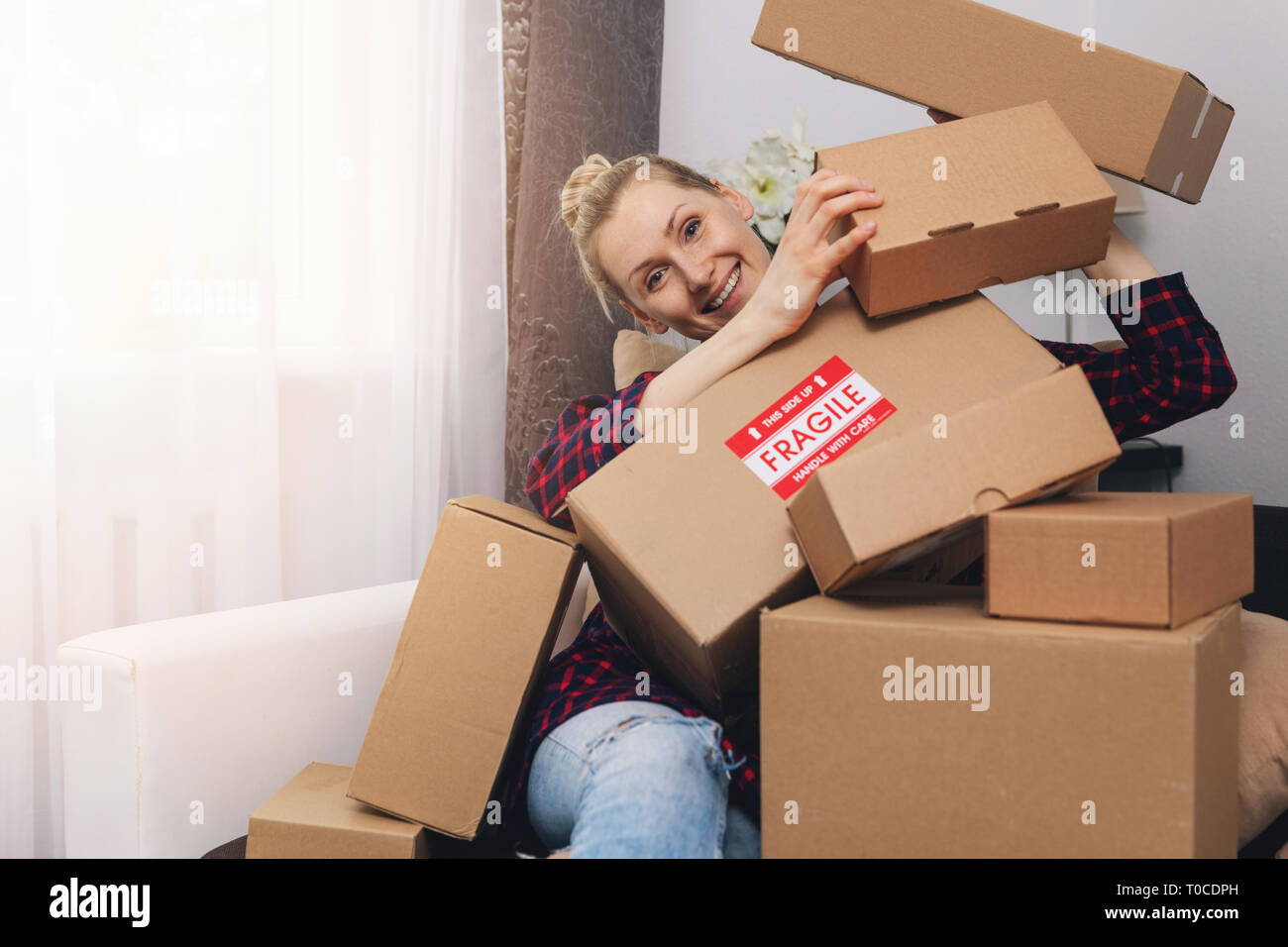 consumerism concept - happy woman with cardboard boxes at home after shopping - Stock Image