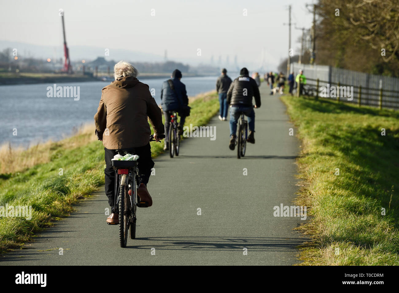 Cyclists on the shared cycling and pedestrian path alongside the River Dee at Ferry Lane heading out of Chester towards North Wales UK Stock Photo