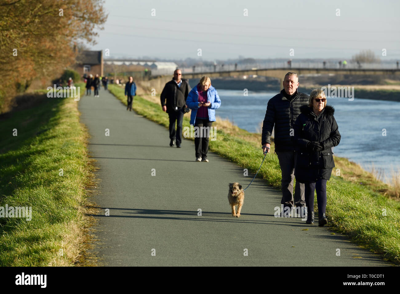 Pedestrians and dog walkers on the path alongside the River Dee at Ferry Lane heading out of Chester towards North Wales UK Stock Photo