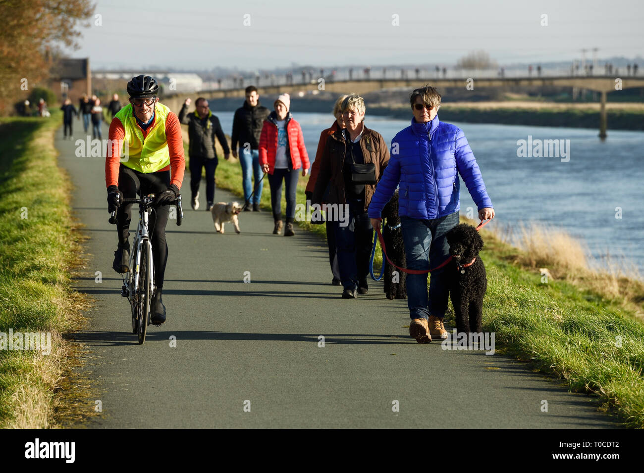 Cyclists, pedestrians and dog walkers on the path alongside the River Dee at Ferry Lane heading out of Chester towards North Wales UK Stock Photo