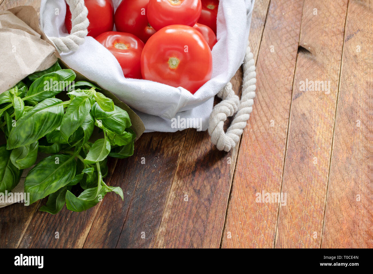 Red tomatoes and green Basil in eco-friendly packaging on wooden table. - Stock Image