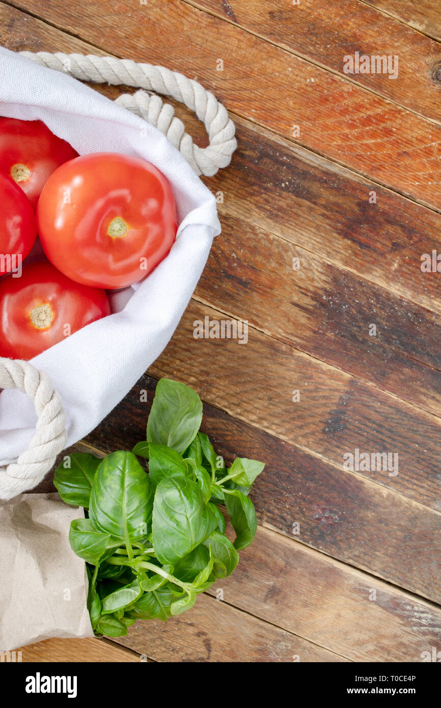 Red  ripe tomatoes and green Basil in ecological  packaging on diagonal wooden table. - Stock Image