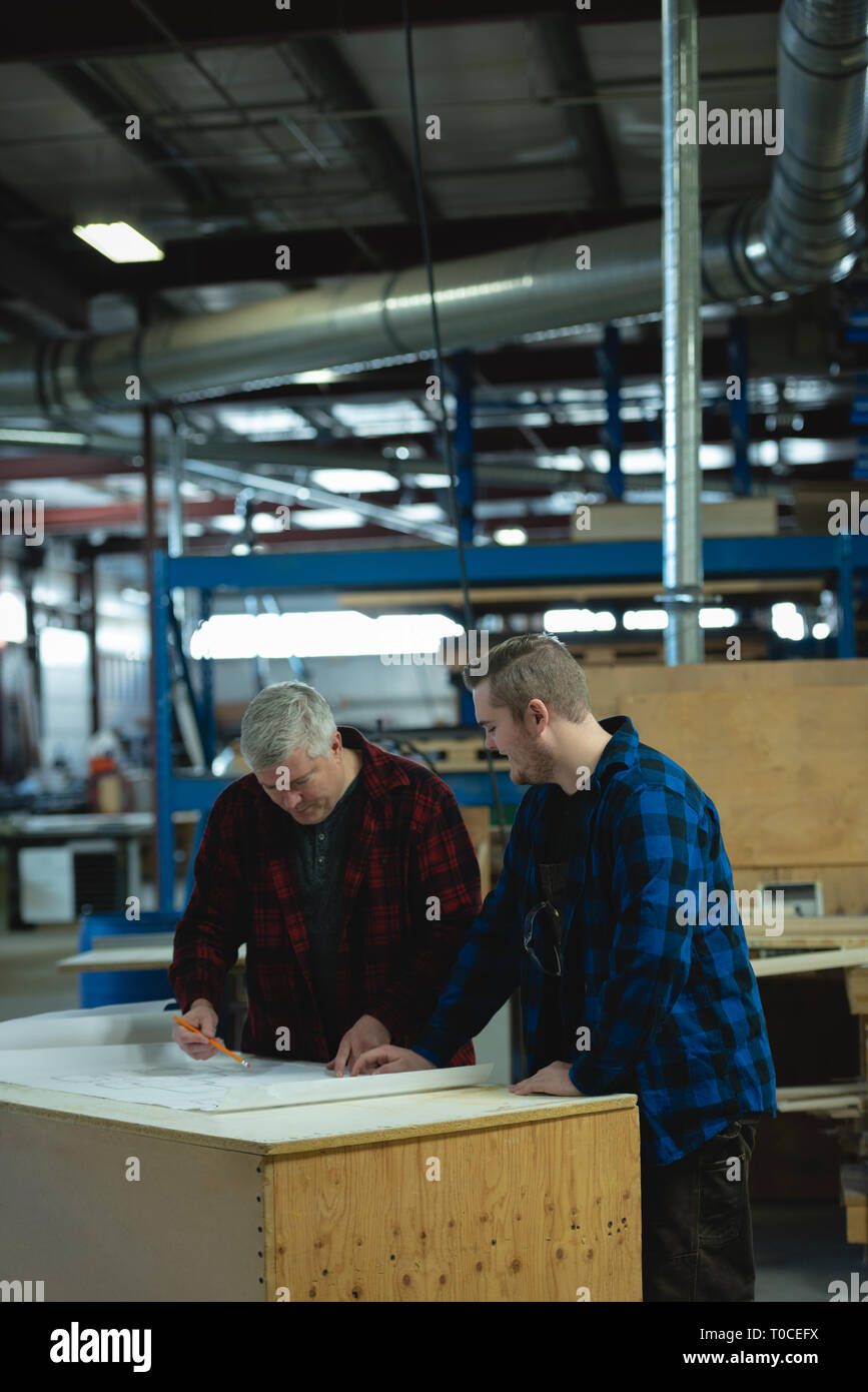 Caucasians male carpenters discussing and measuring at workshop - Stock Image