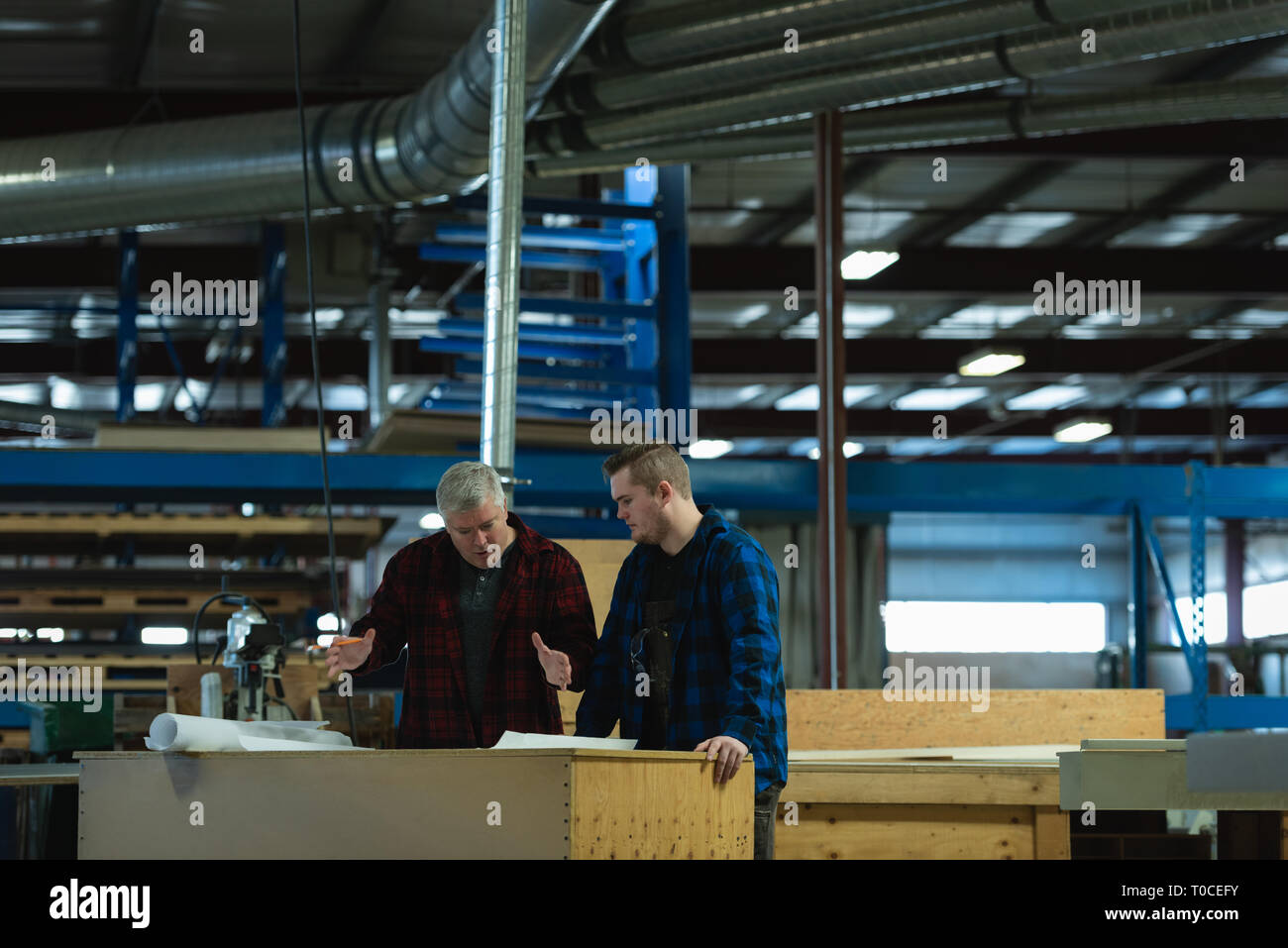 Caucasians male carpenters standing and discussing with each other at workshop - Stock Image