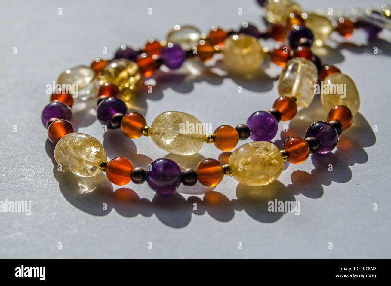 Bracelet and necklace hand made using colourful semi-precious gemstone beads including yellow citrine, purple amethyst and orange carnelian. Stock Photo