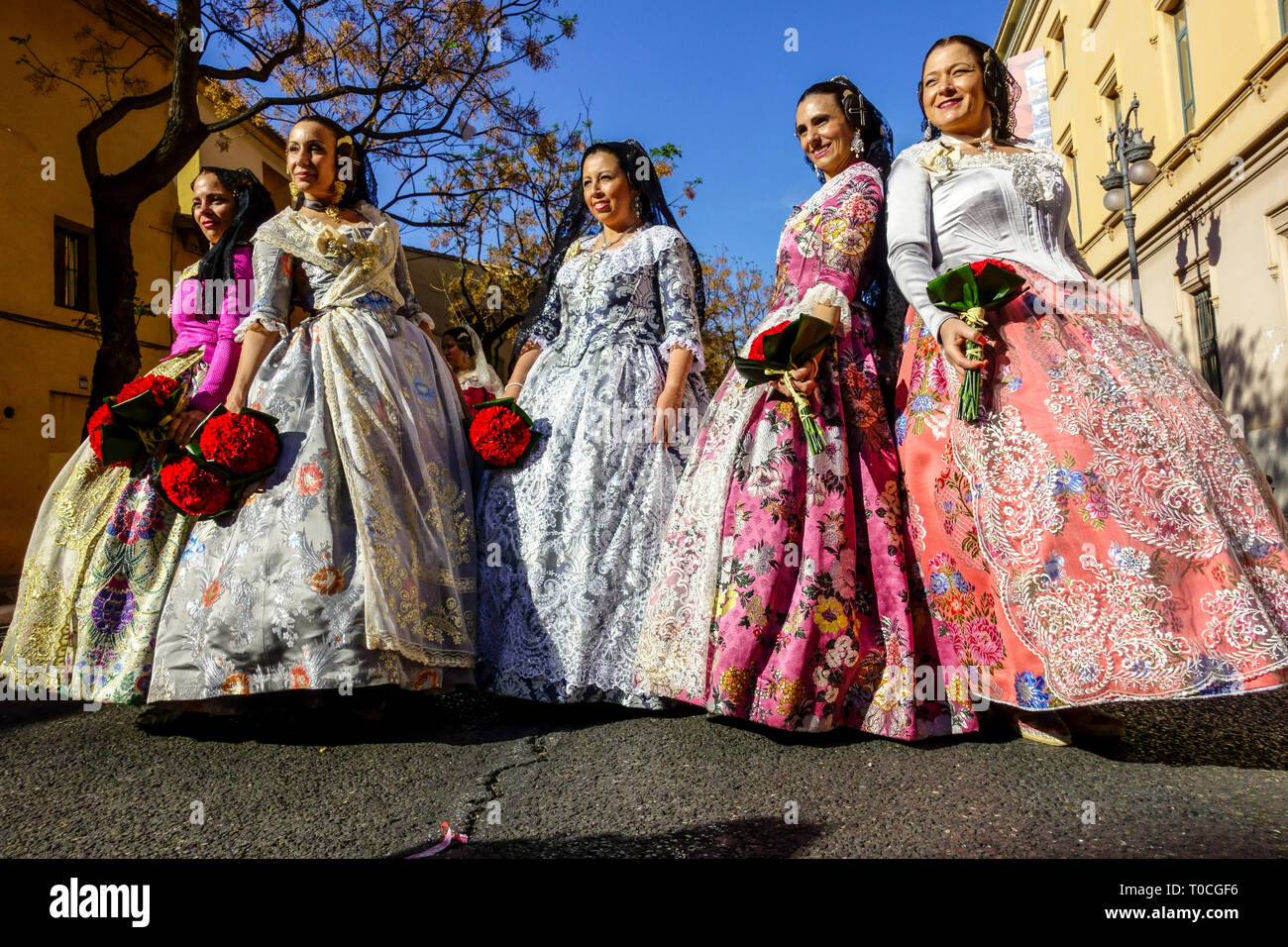 Valencia Fallas, Women in festive folk costumes in procession to the Virgin Mary with flowers to her honor, Spain Stock Photo