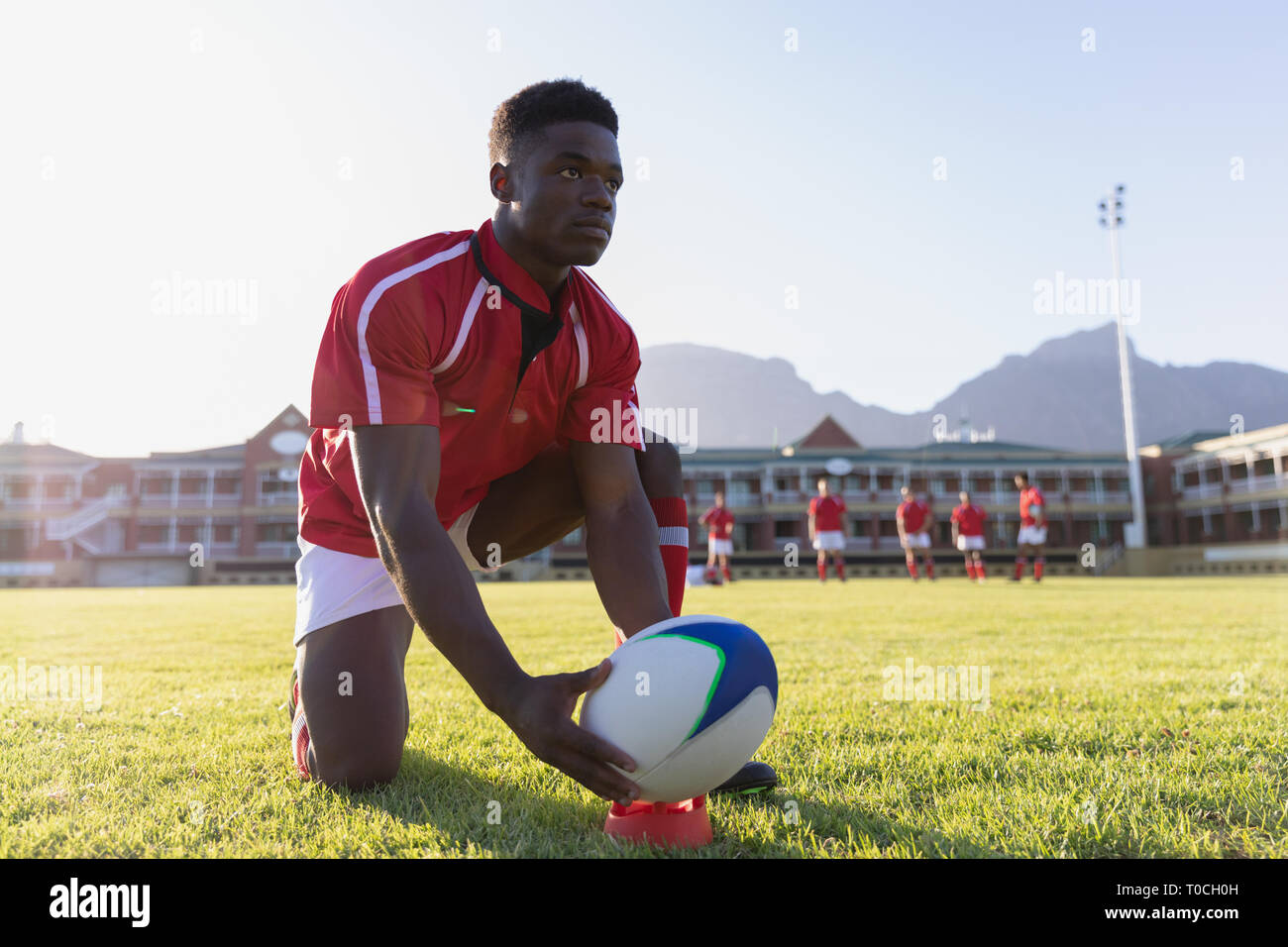 Male rugby player placing rugby ball on a stand in the rugby playground - Stock Image