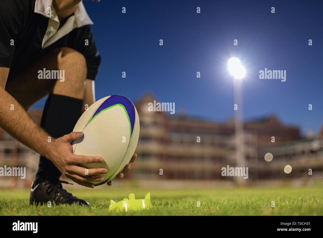 Male rugby player placing rugby ball on a stand in the stadium - Stock Image