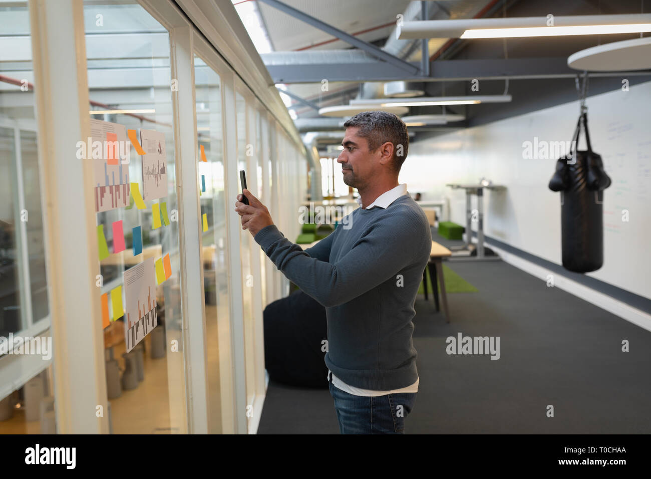 Businessman capturing photos  of stick notes in office - Stock Image