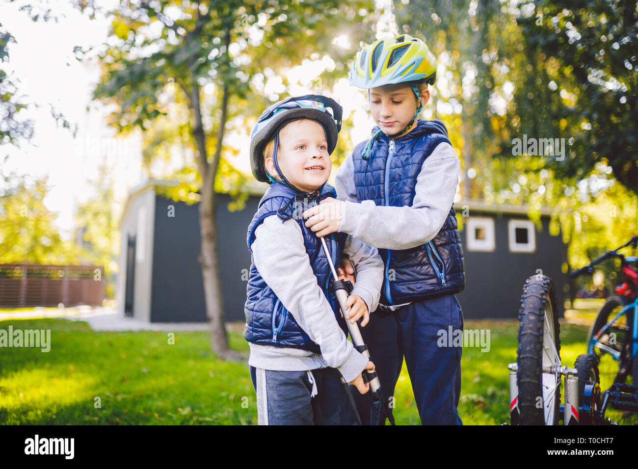 Two children, older boys and younger brother learning repair bike. Two guys siblings in helmets and single clothes use pump tool and pump air into Stock Photo