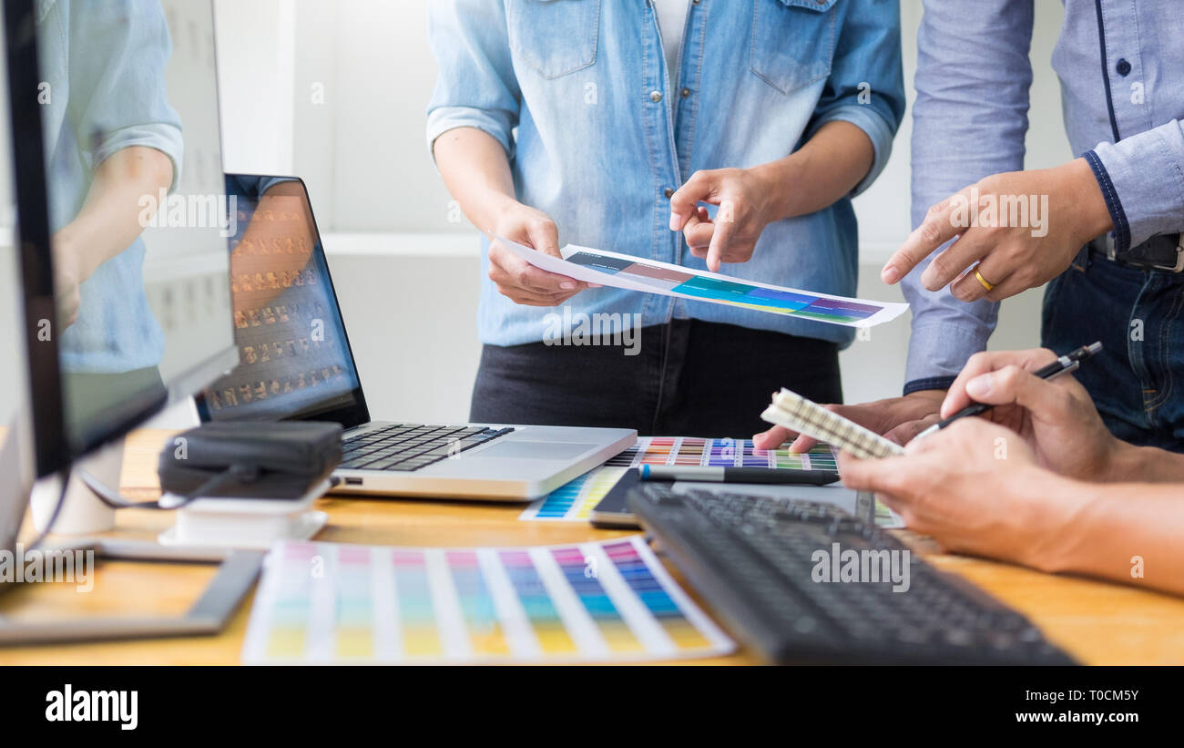 graphic designer team working on web design using color swatches editing artwork using tablet and a stylus At Desks In Busy Creative Office Stock Photo