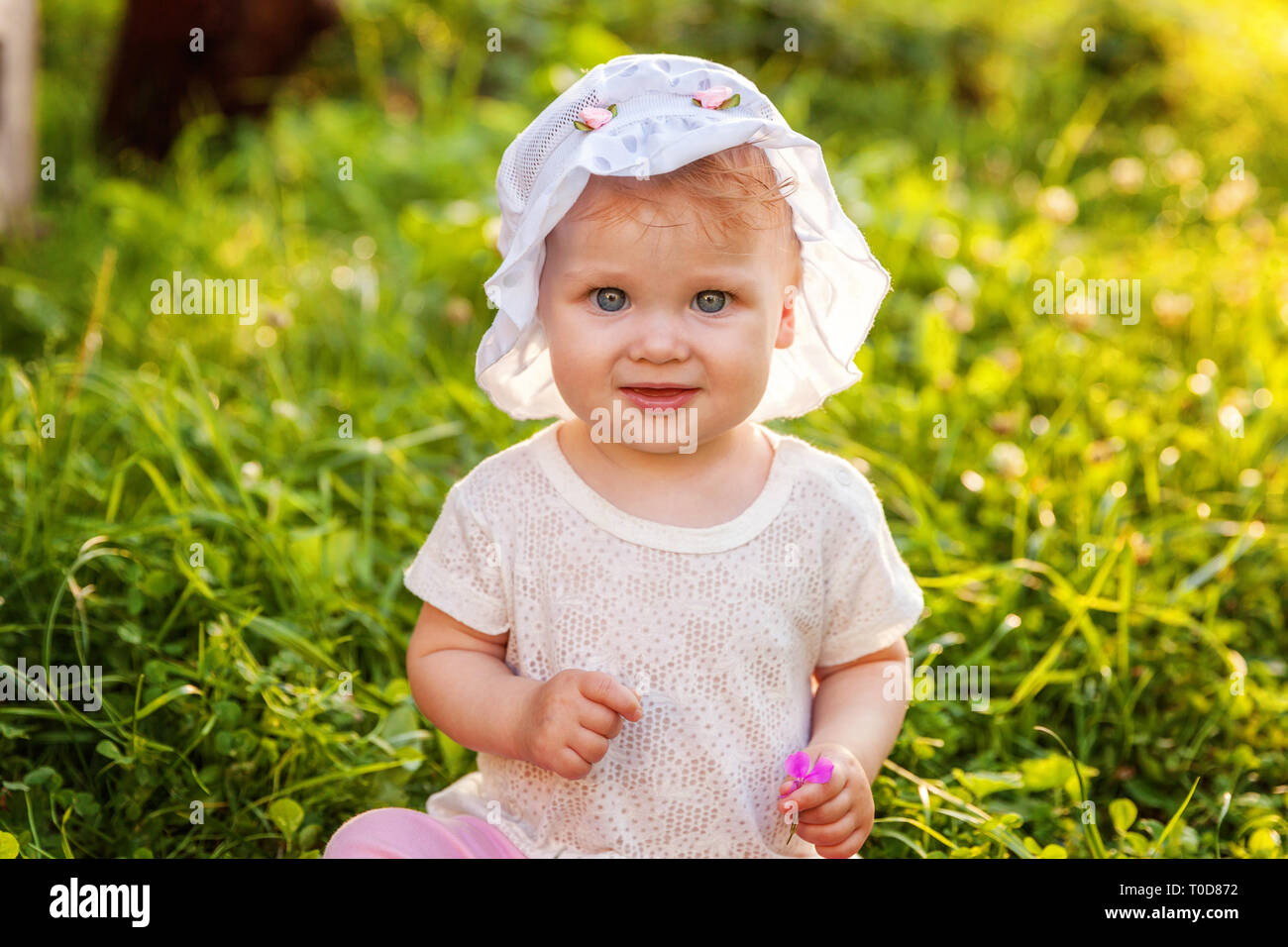 Sweet happy little baby girl sitting on grass in park, garden, meadow. Laughing, happiness, enjoying fresh air in forrest in sunny summer day. Portrai Stock Photo