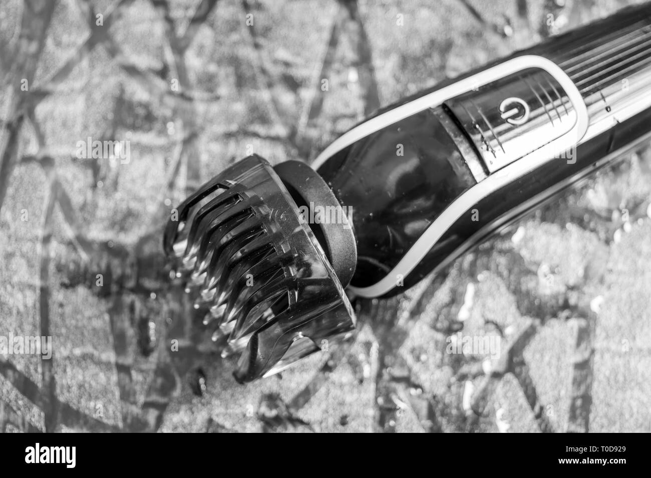 Man's electric shaving machine or trimmer with a blade adjustment comb kept on a wet floor - Stock Image