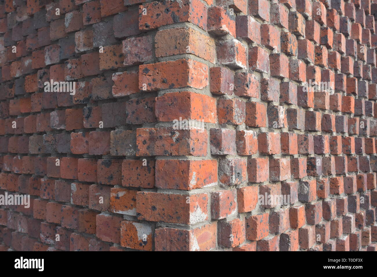 Corner detail of exterior wall of red bricks and mortar with bricks protruding form wall surface. - Stock Image