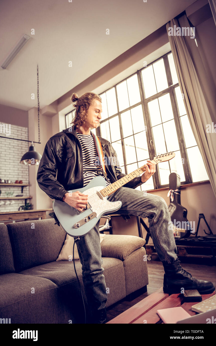 Musician with hair bun getting much satisfaction playing rock music - Stock Image
