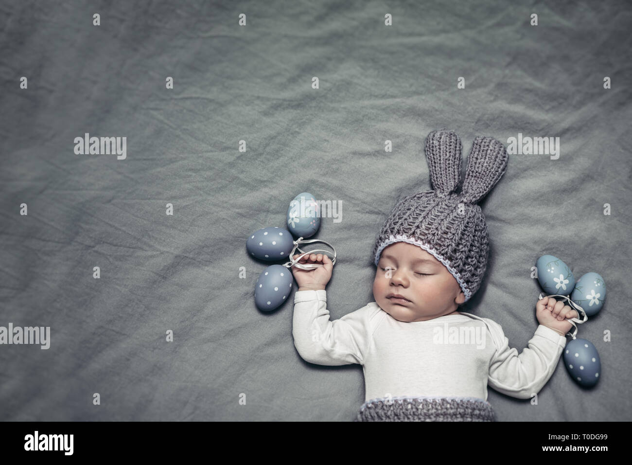 ff331dd88eb2 Portrait of an adorable newborn child dressed in a knitted costume of an Easter  bunny with